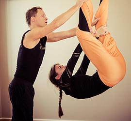 Jost Blomeyer hilft Teilnehmerin im Aerial Yoga Kurs